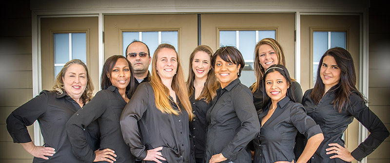 Photo of the Day & Night Family Dental team standing in front of the dental office
