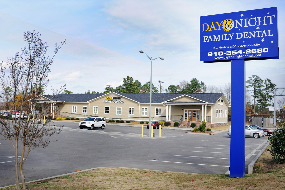 Photo of the exterior of the Day & Night Family Dental office, including the sign and parking lot