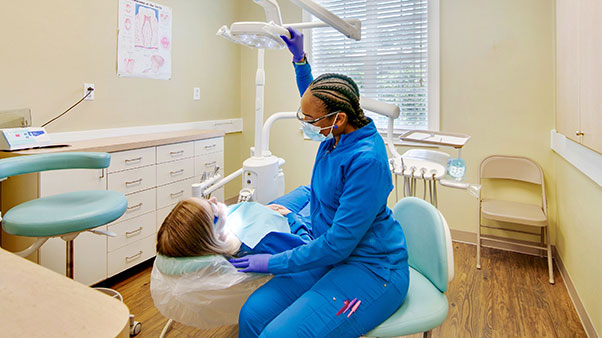 dental hygienist cleaning teeth of patient